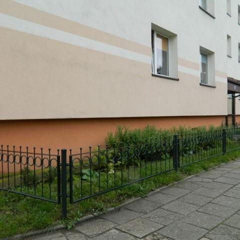 niskie metalowe ogrodzenie bloku